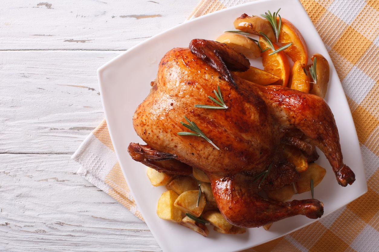baked whole chicken with oranges on plate. horizontal top view