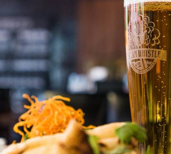 Steam Whistle beer with a plate of food