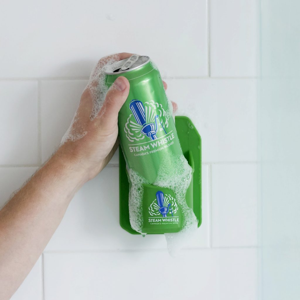 A picture of the Steam Whistle silicon Shower Caddy attached to a shower white tile wall, holding a can of Steam Whistle Pilsner. It is covered in soap suds and a man's hand is reaching for the can. Description automatically generated